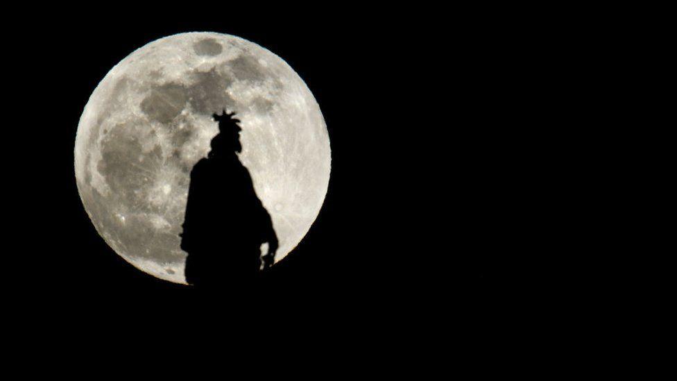 Vista de la luna de sangre de lobo tras la estatua del Capitolio de Estados Unidos.