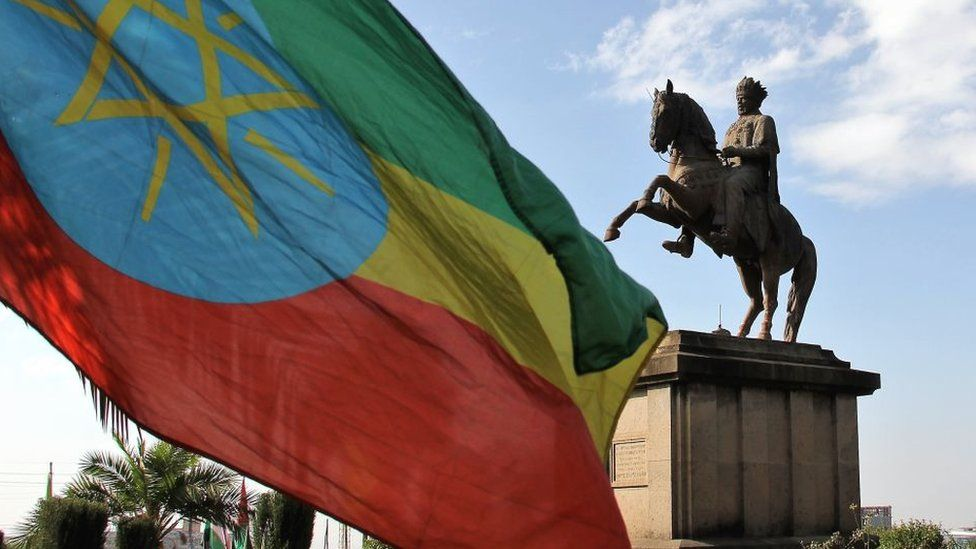 A statue of Menelik II and the Ethiopian flag in Menelik Square, Addis Ababa, Ethiopia