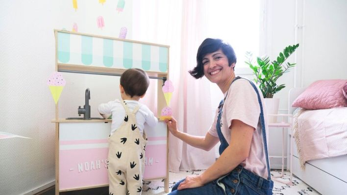 A woman and child stand next to wall stickers