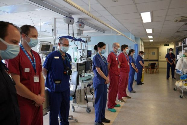 Nurses and firefighters stand alongside each other in an ICU ward
