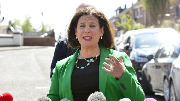 Sinn Féin leader Mary Lou McDonald, pictured outside on a sunny day, standing in front of a microphone and wearing a green jacket, while gesturing with her hand