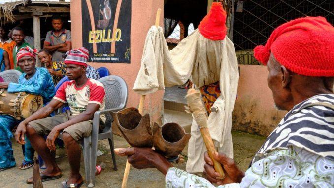 Men sat during an Igbo meeting
