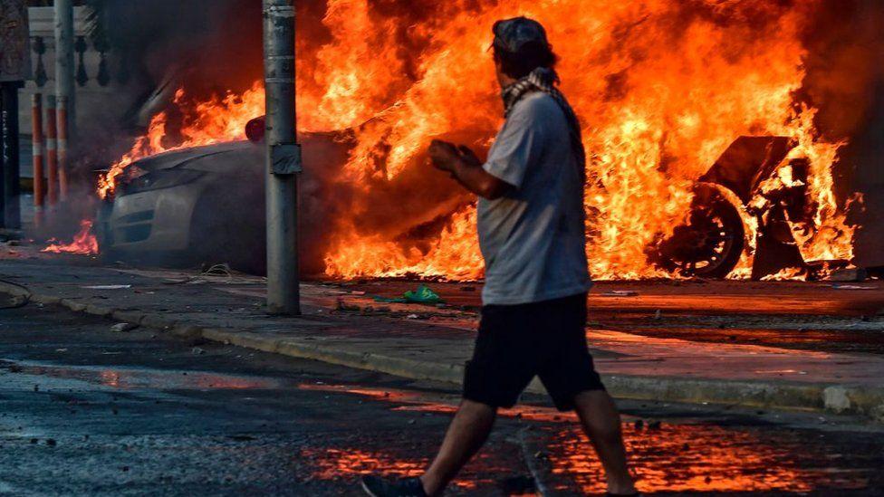 Carro en fuego y manifestante en primer plano.