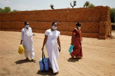 Healthcare workers arrive with doses of COVISHIELD, a coronavirus disease (COVID-19) vaccine manufactured by Serum Institute of India, to be administered to workers of a brick kiln at Kavitha village on the outskirts of Ahmedabad, India, April 8, 2021.