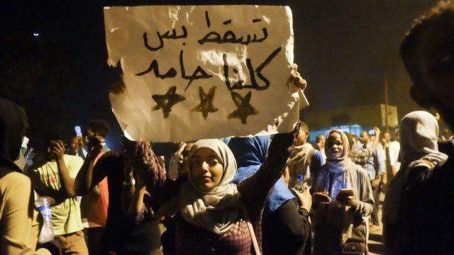 """A woman holds up a sign reading: """"We are all Hamid"""" at a sit-in at the military HQ in Khartoum, Sudan - Monday 8 April 2019"""