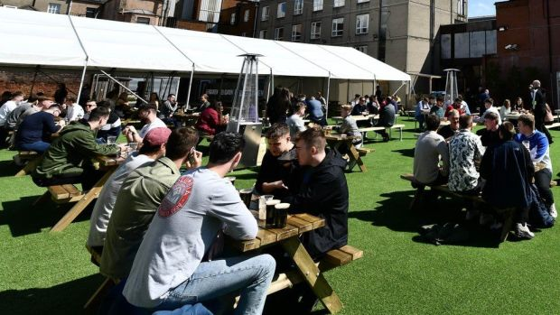 People drinking at an outdoor bar in Belfast