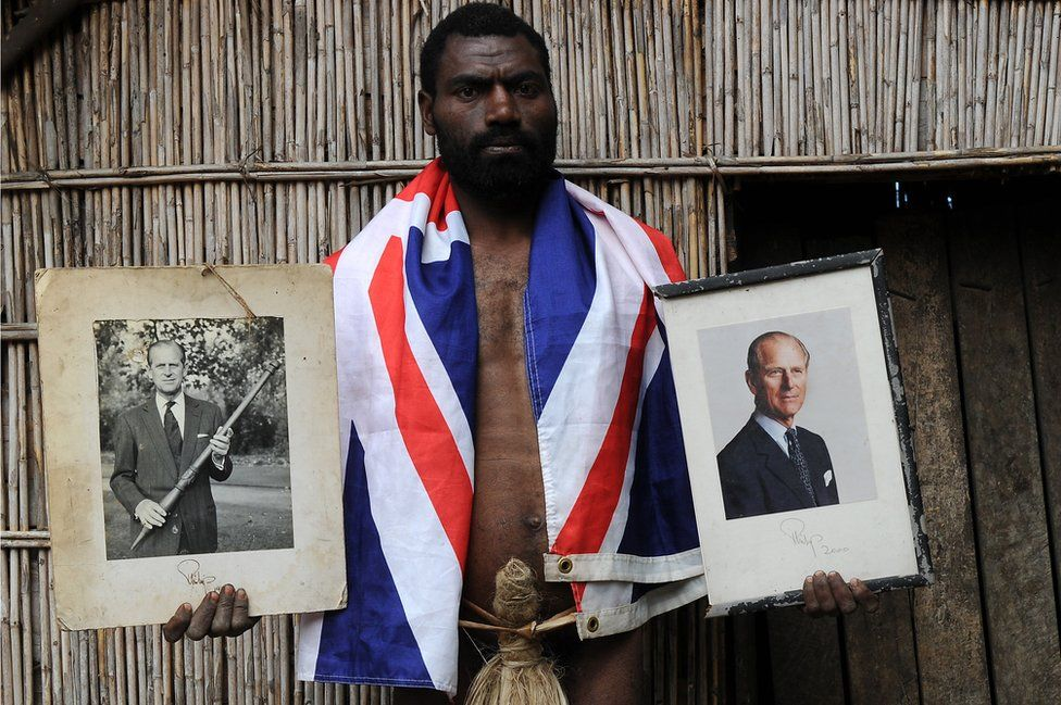 Tribesman Sikor Natuan holds two portraits of Britain's Prince Philip in front of the chief's hut in the remote village of Yaohnanen on Tanna island in Vanuatu