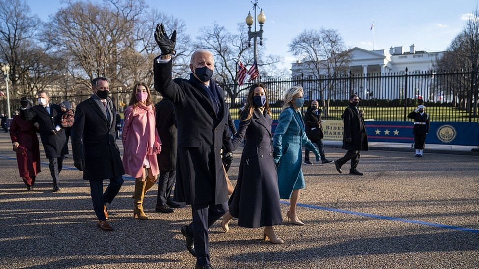 US President Joe Biden and First Lady Jill Biden walk along Pennsylvania Avenue in front of the White House, in Washington, DC, 20 January 2021