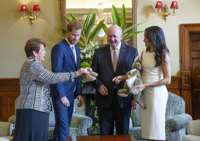 "Australian Governor-General Sir Peter Cosgrove (2-R) and his wife Lady Cosgrove (L) present a toy kangaroo and a pair of small ugg boots to Britain""s Prince Harry (2-L), the Duke of Sussex, and his wife Meghan (R), the Duchess of Sussex, during an event at Admiralty House in Sydney, Australia, 16 October 2018"