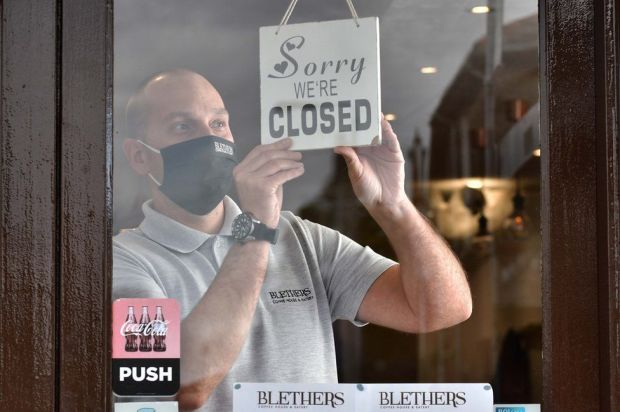 A cafe worker puts up a sign that reads: Sorry, we're closed