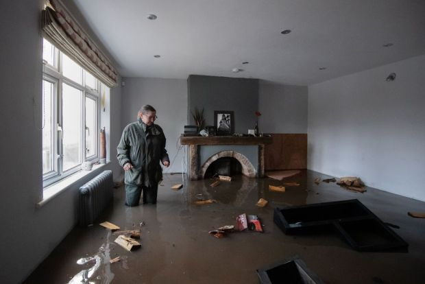 A woman stands in her flooded home on the outskirts of Lymm in Cheshire, 21 January 2021
