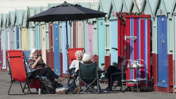 Members of the University of the Third Age iPhone photography group have an impromptu get together at beach huts in Hove, East Sussex