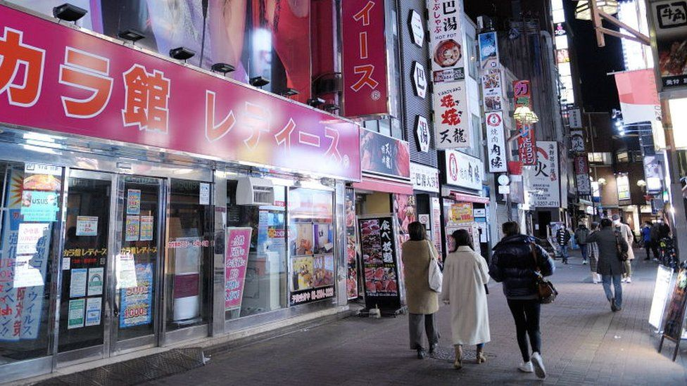People walk past the entrance of an Karaoke store closed due to the spread of the conoravirus in Tokyo