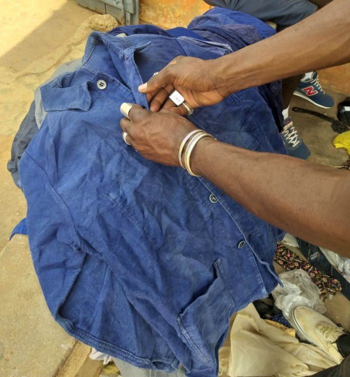 Amah Ayivi selects a blue worker jacket.