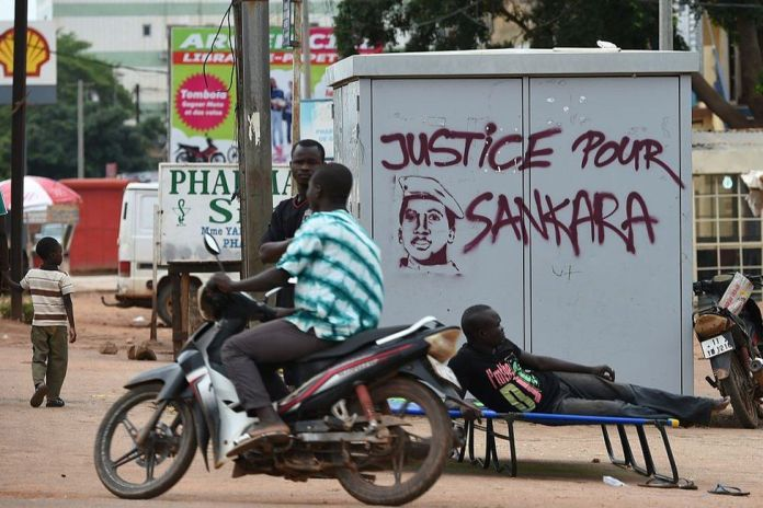 """People stand next to graffiti that reads """"justice for Sankara""""."""