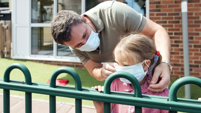 Stock image of a father and child at school