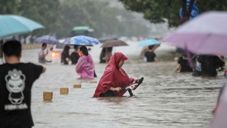 This photo taken on July 20, 2021 shows people wading through flood waters along a street following heavy rains in Zhengzhou