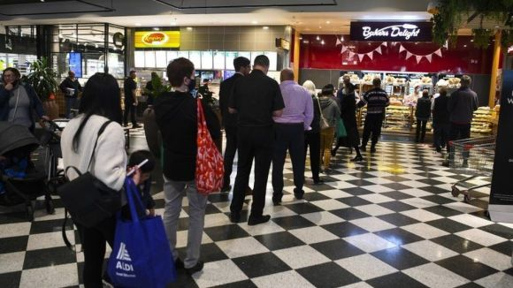 Customers stand in long lines at a check out counter at a bakery in the Woden area in Canberra, Australian Capital Territory, Australia