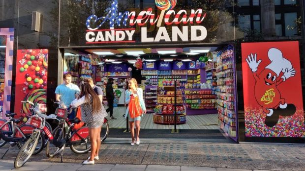 People stand outside an American Candy Land shop on Oxford Street