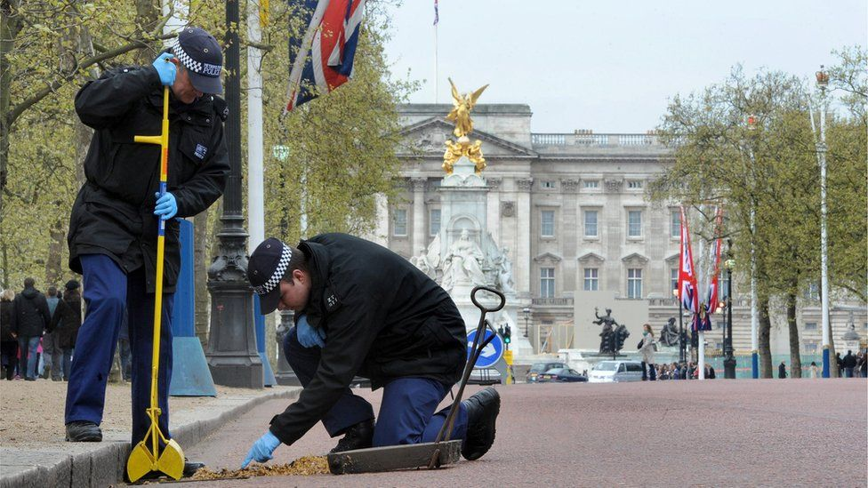 Two police officers carrying out security checks outside Buckingham Palace