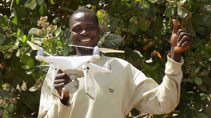 A cashew farmer in Benin with a drone supplied by TechnoServe