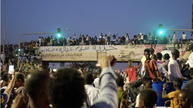 """The banner reading: """"Freedom, peace and justice"""" at a sit-in at the military HQ in Khartoum, Sudan - Sunday 7 April 2019"""