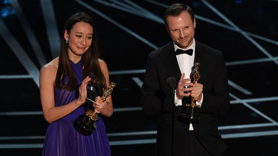 British producer Joanna Natasegara and British director Orlando von Einsiedel stand on stage after they won the Best Documentary Short award for The White Helmets