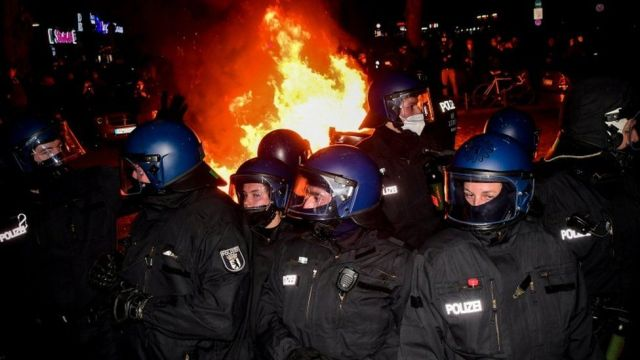 Riot police take position next to a burning barricade during a protest on May Day in Berlin, Germany