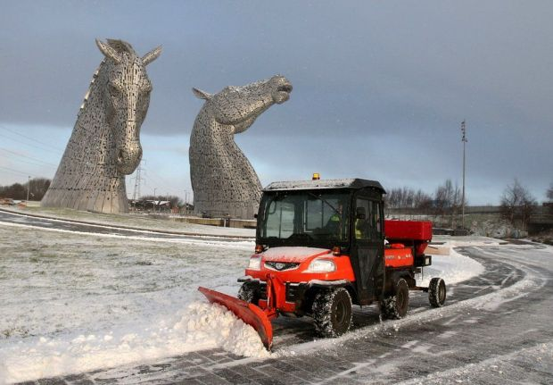 A staff member uses a vehicle to clear snow on a pathway at the Kelpies near Falkirk in Scotland, on 8 February 2021