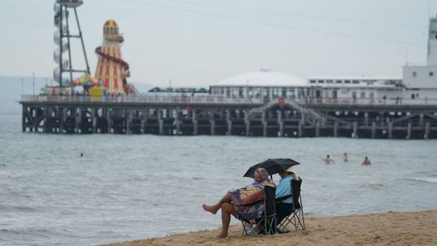 A couple shelter beneath an umbrella at Bournemouth beach in Dorset. The UK has recorded its third successive warmest day of the year