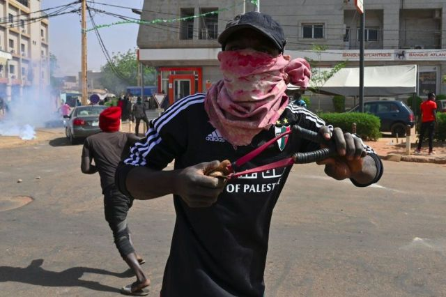 A masked man readies a slingshot on a street with protesters and tear gas behind him.