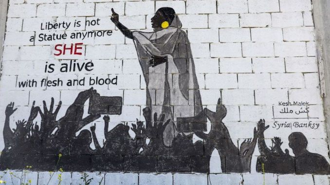 """A mural painting of Alaa Salah painted by a Syrian artists collective called """"Kesh Malek"""" (Checkmate) on the wall of a farmhouse building in the rebel-held Syrian town of Kafranbel in the north-western Idlib province - 12 April 2019"""