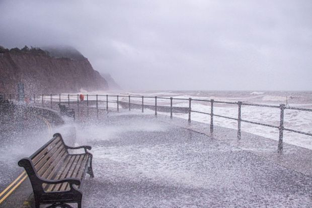 The sea bursts on to a deserted esplanade at Sidmouth, Devon