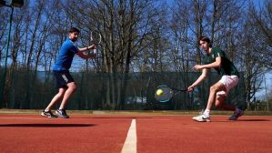 Two people playing tennis outdoors
