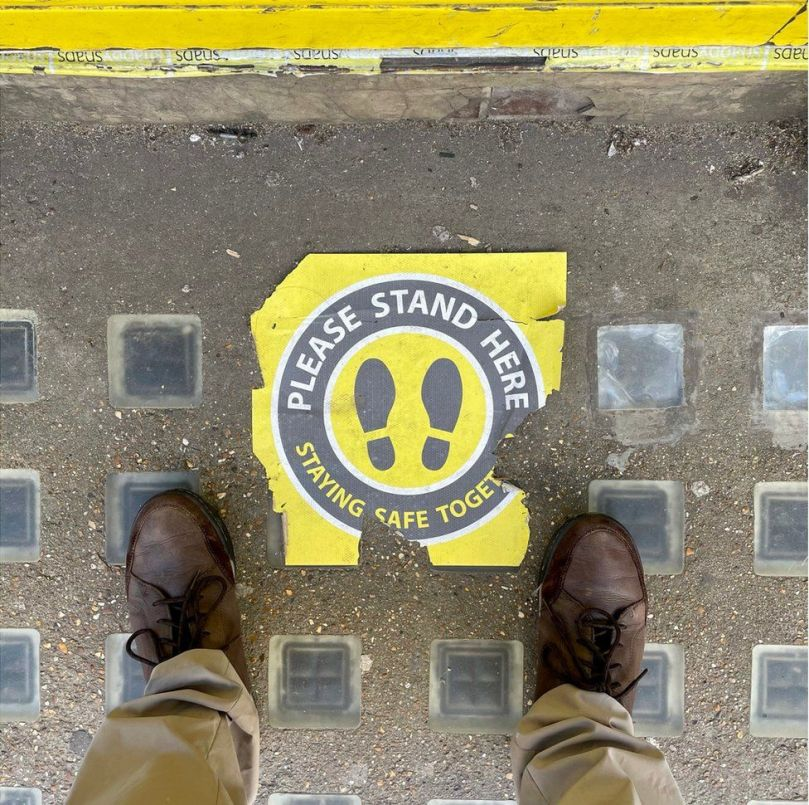 A yellow and black sign on the ground that askes people to stand on it whilst queuing
