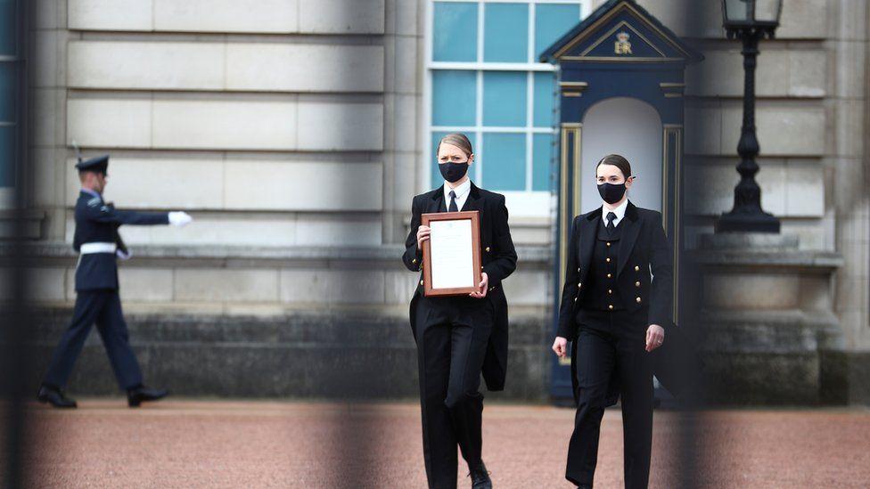 Medewerkers brengen een bericht naar het hek van Buckingham Palace nadat was aangekondigd dat Prins Philip was overleden