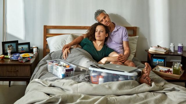 Jennifer Brea and Omar Wasow in bed, surrounded by medication