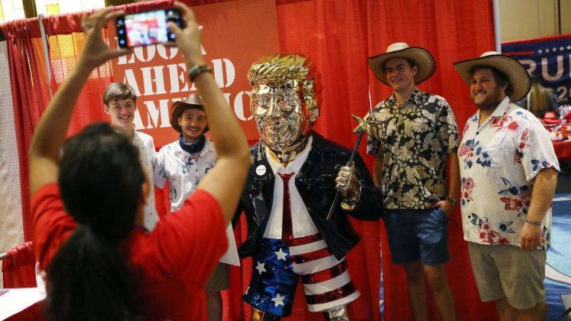 Cpac attendees pose with a gold statue of Donald Trump