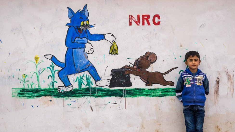 A child in Domiz Syria refugee camp in 2014 stands next to a mural of Tom and Jerry. NRC stands for Norwegian Refugee Council