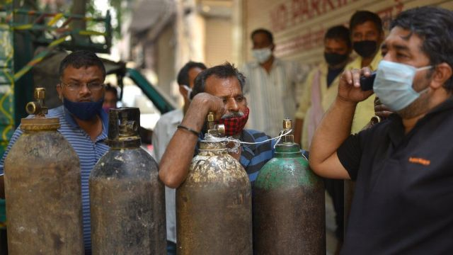 People wait to fill their oxygen cylinders at an oxygen vendor in New Delhi