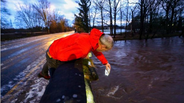Council worker in Didsbury, Manchester checks a bridge for damage