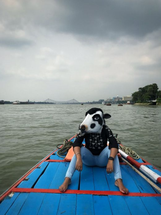 A woman with a cow mask on a boat
