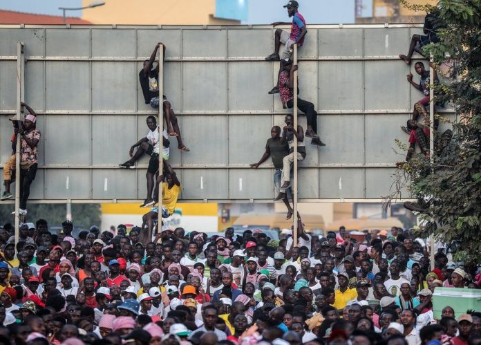 People clinging on to a billboard during a rally for presidential candidate Idrissa Djalo in Bissau, Guinea-Bissau - Tuesday 19 November 2019