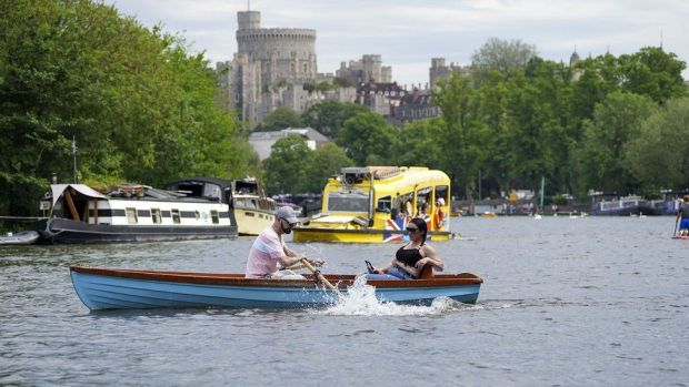 People enjoy boats on the River Thames in Windsor, Berkshire