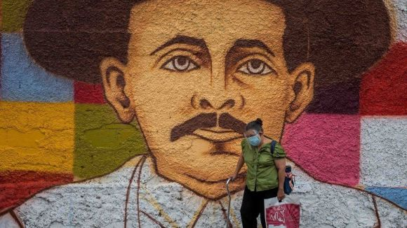 A woman walks by a mural of Jose Gregorio Hernandez, in Caracas