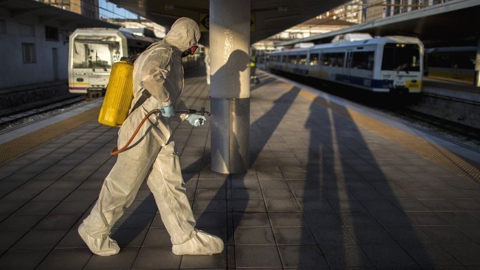 A health worker sprays a train station in Spain