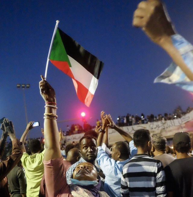 A woman holding up a Sudanese flag at a sit-in at the military HQ in Khartoum, Sudan -Sunday 7 April 2019