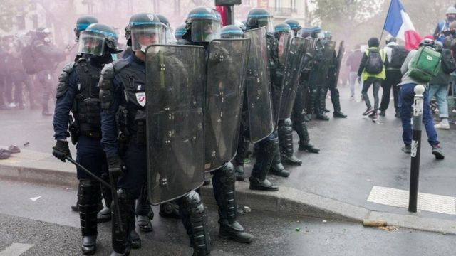 French riot police stand in formation during clashes with protesters in France