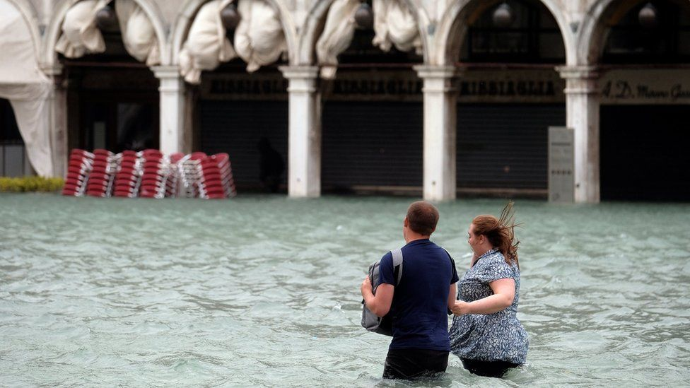 Couple walk in flooded St Mark Square in Venice on 29 October 2018