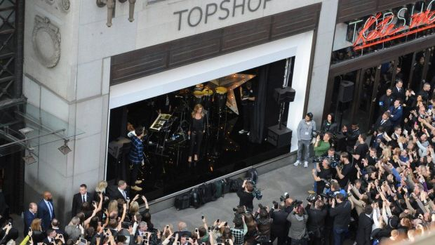 Kate Moss stands in a window of Topshop in 2014